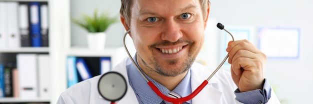 Przystojna samiec lekarka stawia dalej stetoskopu portret