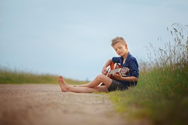 Przystojna śliczna chłopiec bawić się na akustycznej gitary sittingon drodze w letnim dniu.