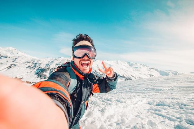 Przystojna śmieszna narciarka bierze selfie w zimie w śniegu na górze
