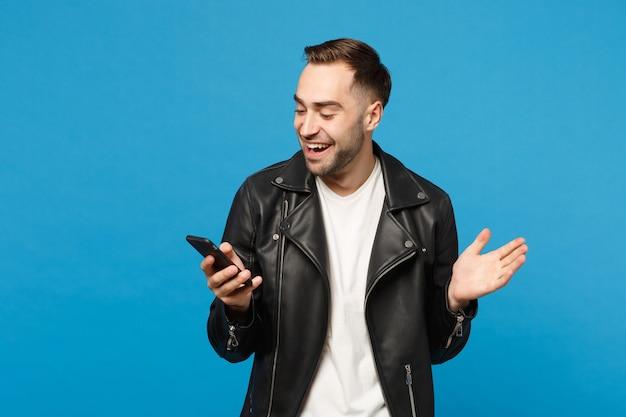 Przystojna zabawa zachwycony podekscytowany młody nieogolony mężczyzna w czarnej skórzanej kurtce biały t-shirt przy użyciu telefonu komórkowego na białym tle na tle niebieskiej ściany portret studio. koncepcja stylu życia ludzi makieta miejsca na kopię