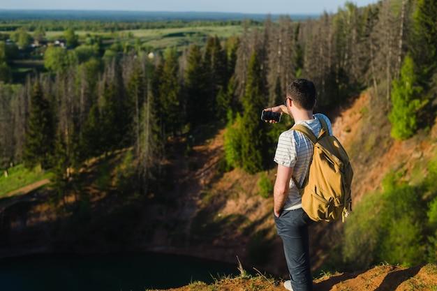 Przystojnego mężczyzna mknący selfie w naturze. piesza wycieczka. chwile wspinaczki. fotografowanie pięknych widoków krajobrazów leśnych.