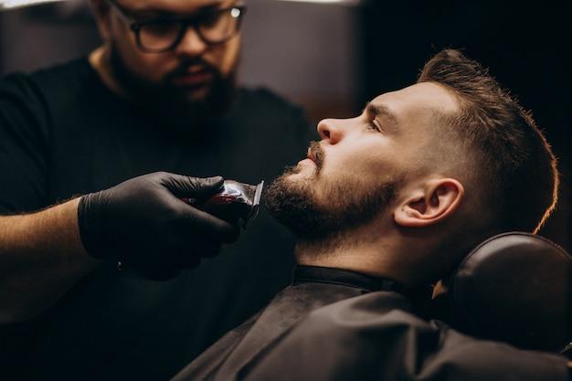 Przystojnego mężczyzna tnąca broda przy fryzjera męskiego salonem
