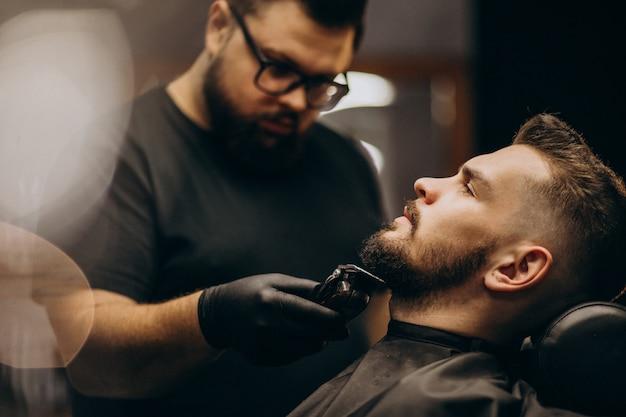 Przystojnego mężczyzna tnąca broda przy fryzjera męskiego sklepu salonem