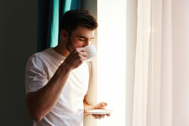 Przystojnej brunetki mężczyzna brodaci stojaki przed jaskrawym okno i napojami kawowymi