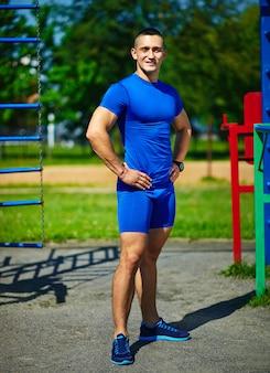 Przystojnej zdrowej srtong atlety męski mężczyzna ćwiczy przy miasto parkiem - sprawności fizycznych pojęcia na pięknym letnim dniu blisko horyzontalnego baru