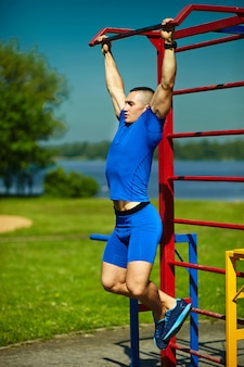 Przystojnej zdrowej szczęśliwej srtong atlety męski mężczyzna ćwiczy przy miasto parkiem - sprawności fizycznych pojęcia na pięknym letnim dniu na horyzontalnym barze