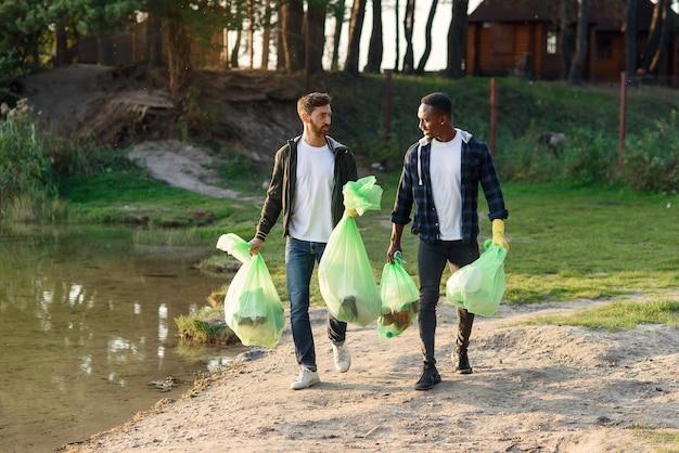 Przystojni, aktywni przyjaciele rasy mieszanej niosący plastikowe torby w pobliżu jeziora po oczyszczeniu otaczającego terytorium ze śmieci.