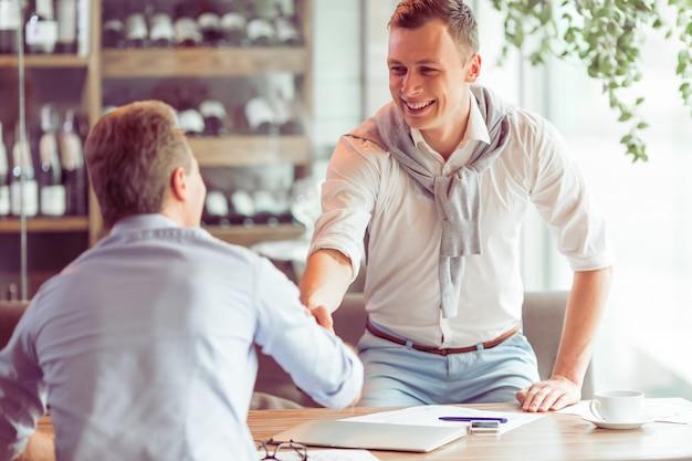 Przystojni biznesmeni spotykają się do pracy w restauracji