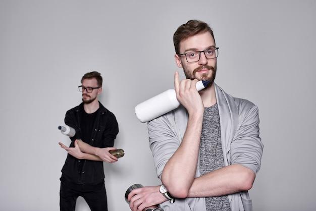 Przystojni brodaci barmani bliźniacy żonglują z wytrząsaczem i butelkami na szarej ścianie