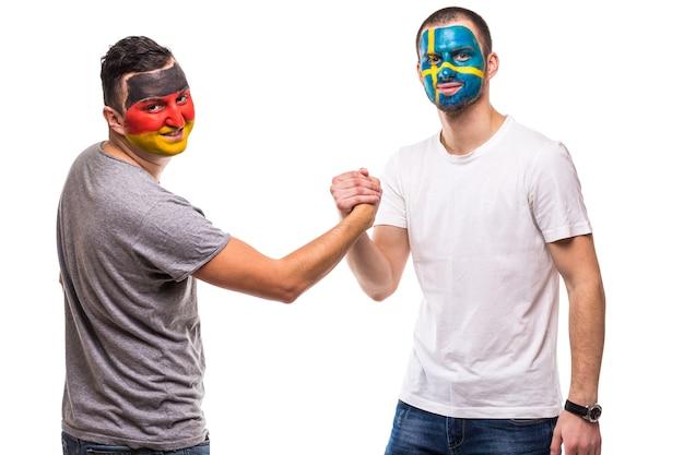 Przystojni mężczyźni kibice lojalni fani reprezentacji szwecji i niemiec z uściskiem dłoni pomalowanej flagi na białym tle. emocje fanów.