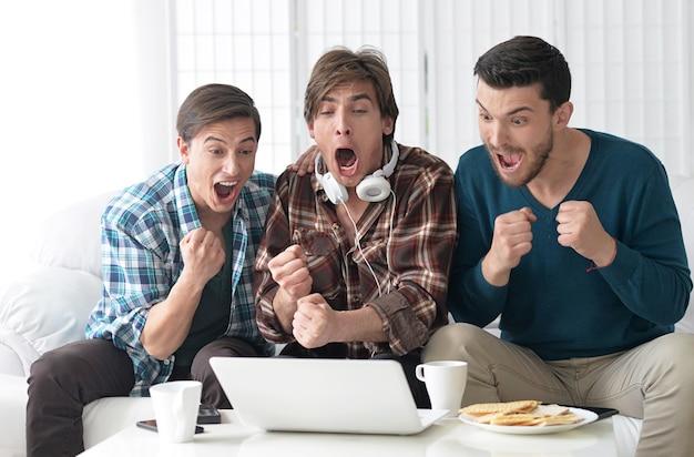 Przystojni mężczyźni razem oglądają wideo na laptopie