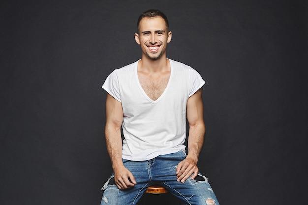Przystojni, muskularni młodzi mężczyźni z brodą, w białej koszulce i modnych dżinsach siedzi na krześle, uśmiecha się i pozuje na czarnym tle