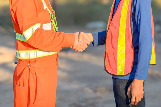 Przystojni pracownicy budowlani w hełmach i kamizelkach ochronnych podają sobie ręce podczas pracy w centrum biurowym