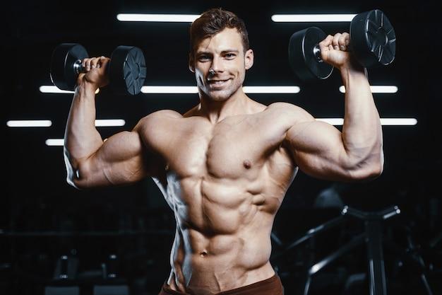Przystojni silni atletyczni mężczyzna pompuje mięśnie treningu bodybuilding