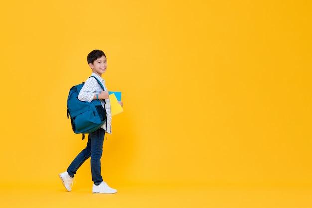 Przystojny 10-letni uczeń trzymający książki i plecak