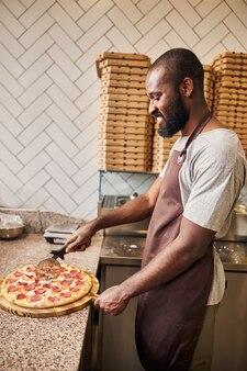 Przystojny afro amerykanin w fartuchu krojący pizzę z okrągłym kółkiem tnącym i uśmiechnięty?