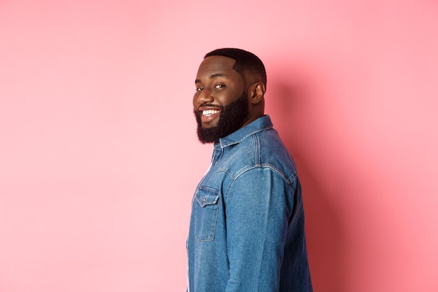 Przystojny afro-amerykanin z brodą, odwracając twarz przed kamerą i uśmiechający się pewnie, stojąc na różowym tle
