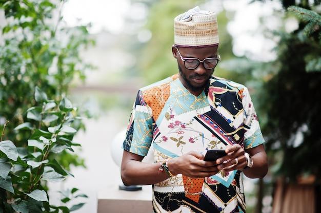 Przystojny afro amerykański mężczyzna nosi tradycyjne ubrania, czapkę i okulary w nowoczesnym mieście, patrząc na swój telefon komórkowy.