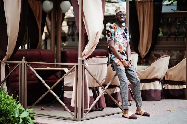 Przystojny afro amerykański mężczyzna nosi tradycyjne ubrania, czapkę i okulary w nowoczesnym mieście.