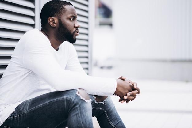 Przystojny afro amerykański mężczyzna noszenie casual ubrania w nowoczesnym mieście siedzi w pobliżu budynku