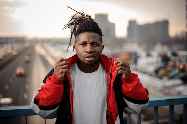 Przystojny afro-amerykański mężczyzna stojący na drodze miasta i zakładanie kurtki