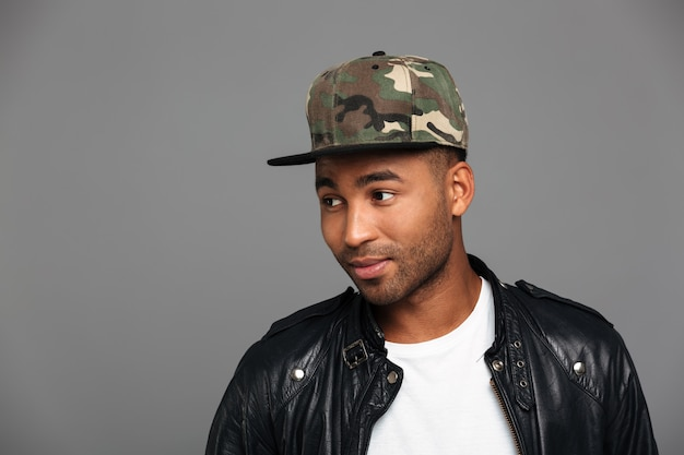 Przystojny afro amerykański mężczyzna w czapce kamuflażu, patrząc na bok