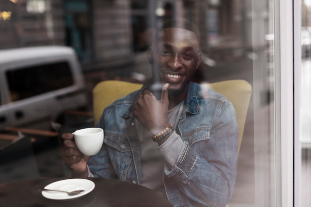 Przystojny afroamerican mężczyzna pozuje przez okno