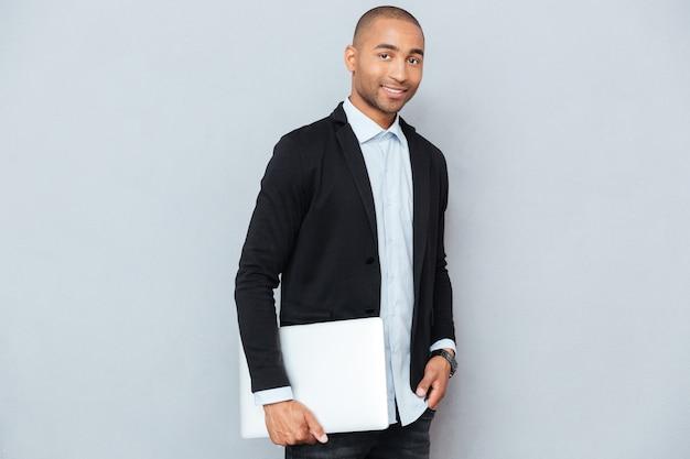 Przystojny afroamerykanin młody mężczyzna stojący i trzymający laptopa