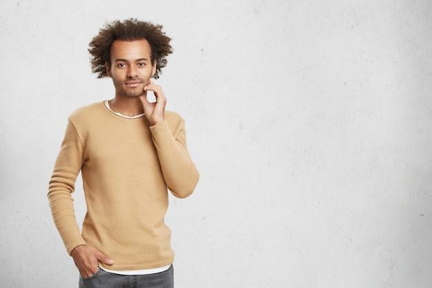 Przystojny afroamerykanin, nieogolony mężczyzna z krzaczastymi włosami, ma pewny siebie wyraz