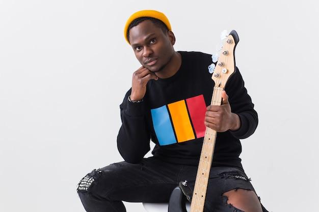 Przystojny afroamerykanin pozowanie w czarnej bluzie z gitarą
