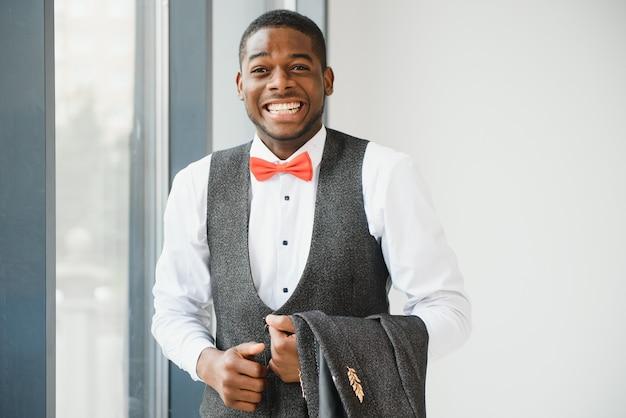 Przystojny afroamerykanin w pobliżu okna w biurze