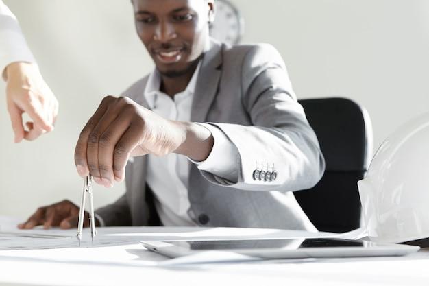 Przystojny afrykański inżynier trzymający kompasy i sprawdzający pomiary projektu budowlanego, podczas gdy jego kaukaski kolega wskazuje palcem na plan, pokazując coś podczas spotkania w biurze