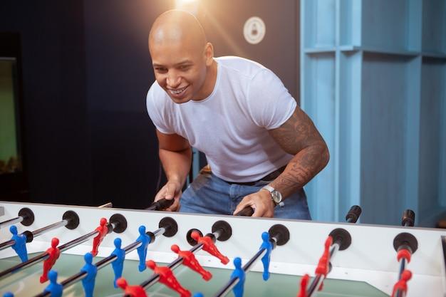 Przystojny afrykański mężczyzna cieszy się bawić się stołową piłkę nożną