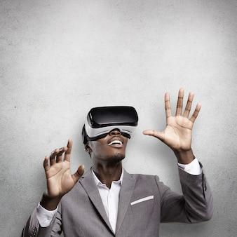 Przystojny afrykański przedsiębiorca ubrany w szary garnitur, gestykulujący i trzymający się za ręce, jakby wchodząc w interakcję z czymś podczas grania w gry wideo za pomocą zestawu słuchawkowego wirtualnej rzeczywistości 3d lub okularów oculus