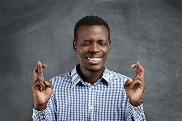Przystojny afrykański student w kraciastej koszuli krzyżuje palce na obu dłoniach i trzyma oczy zamknięte, życząc sobie, mając nadzieję na najlepsze i modląc się o cud, pragnąc zdać egzaminy z wysokimi ocenami