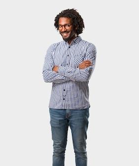 Przystojny afrykańsko-amerykański biznes krzyżuje jego ręki, uśmiechnięty i szczęśliwy