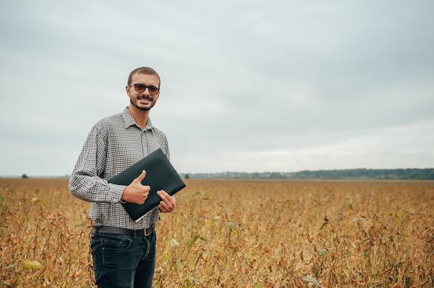 Przystojny agronom trzyma tablet dotykowy na polu soi i bada plony przed zbiorem