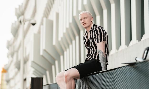 Przystojny albinos siedzący w budynku
