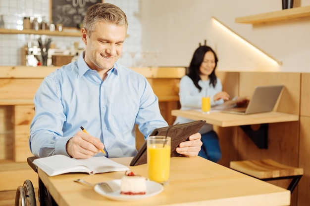 Przystojny alert upośledzony mężczyzna siedzi na wózku inwalidzkim i pisze w swoim notatniku i pracuje na swoim tablecie w kawiarni i kobieta siedzi w tle
