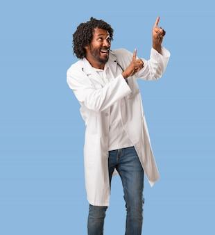 Przystojny amerykanin afrykańskiego pochodzenia lekarz medycyny wskazuje strona, ono uśmiecha się zaskakuję przedstawiać coś, naturalny i przypadkowy