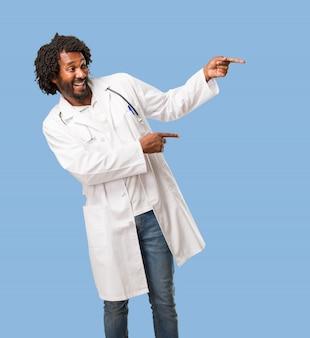 Przystojny amerykanin afrykańskiego pochodzenia lekarz medycyny wskazuje strona, ono uśmiecha się