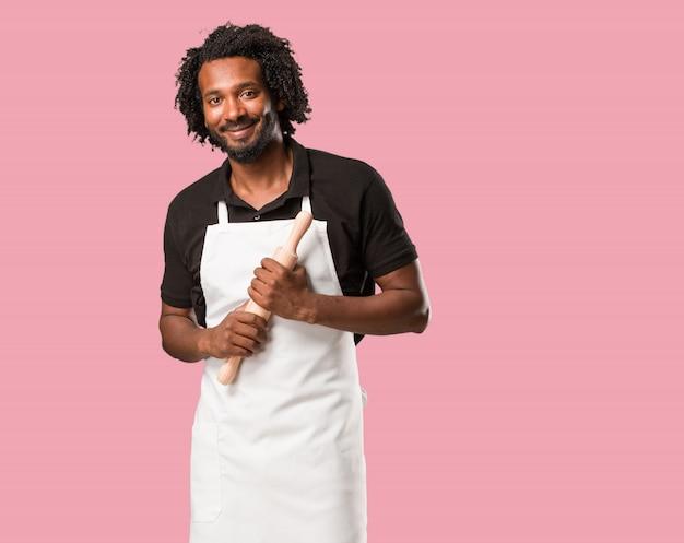Przystojny amerykanin afrykańskiego pochodzenia piekarz krzyżuje jego ręki, uśmiechnięty i szczęśliwy, jest ufny i życzliwy