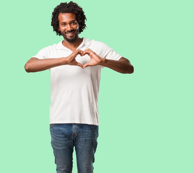 Przystojny amerykanin afrykańskiego pochodzenia robi sercu z rękami, wyrażający pojęcie miłość i fr