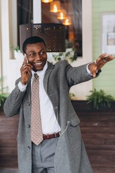 Przystojny amerykanina afrykańskiego pochodzenia biznesmen opowiada na smartphone w restauraci.