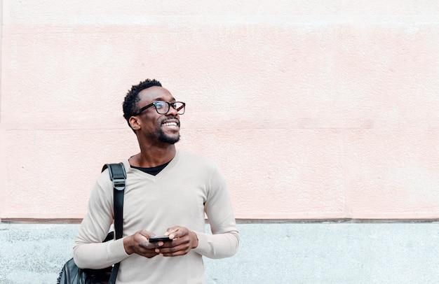 Przystojny amerykanina afrykańskiego pochodzenia mężczyzna używa smartphone na ulicie