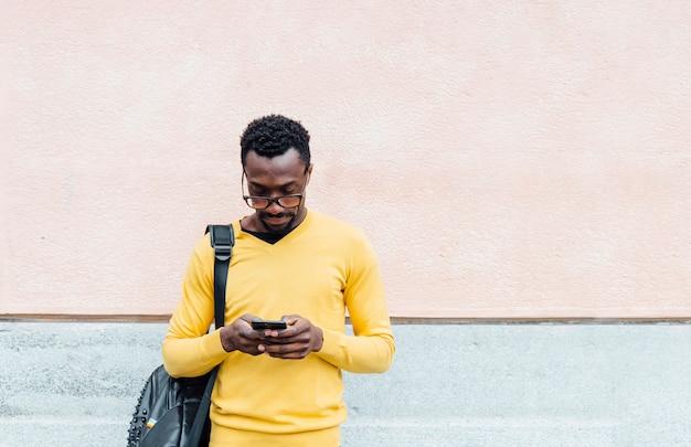 Przystojny amerykanina afrykańskiego pochodzenia mężczyzna używa smartphone.