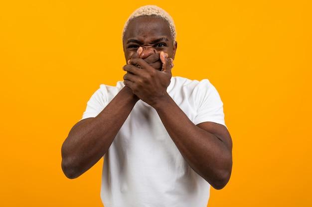 Przystojny amerykański facet w białej koszulce kantuje jego usta z rękami na kolorze żółtym odizolowywającym