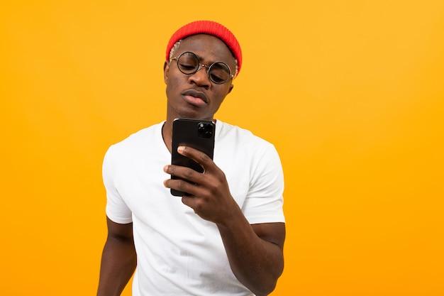 Przystojny amerykański mężczyzna w białej koszulce komunikuje się w sieci społecznościowej na żółto z miejsca kopiowania