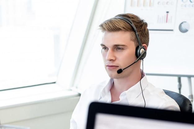 Przystojny angielski biznesmen jest ubranym mikrofon słuchawki pracuje w biurze
