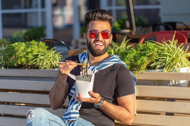 Przystojny arab młody hipster facet jedzenie chińskiego makaronu drewnianymi pałeczkami siedzi w parku na zewnątrz w ciepły letni dzień. pojęcie odpoczynku i podjadania na ulicy.